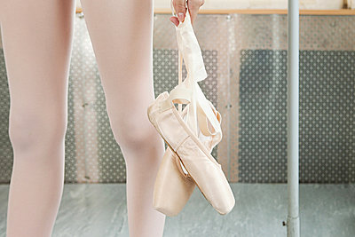 Close up on ballerina holding ballet shoes - p9245516f by Image Source