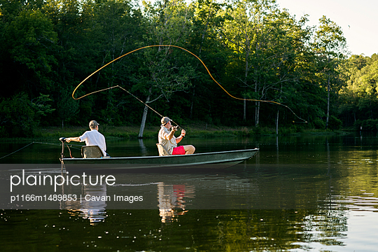 Man casting fishing line in lake with friend sitting in rowboat