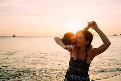 Thailand, Koh Lanta, happy mother with baby girl on her shoulders at seashore during sunset - p300m2070353 von Gemma Ferrando
