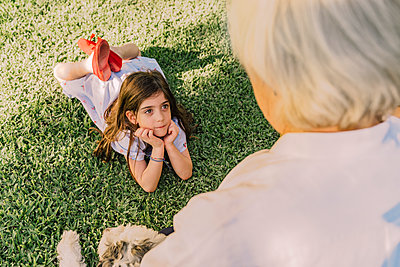 Cute girl with hands on chin looking at grandmother while lying over grassy land in yard - p300m2206692 by Eloisa Ramos