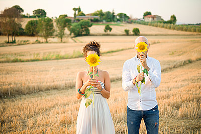 Heterosexual couple in field, holding sunflowers in front of faces - p429m1561760 by Senserini Lucrezia