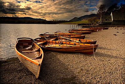 Canoes on the shore, Keswick, Cumbria, England - p4426821f by Design Pics