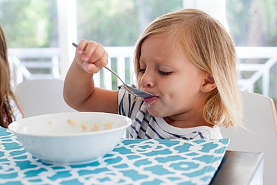 Girl eating breakfast from bowl with spoon - p924m1125796f by Kinzie Riehm