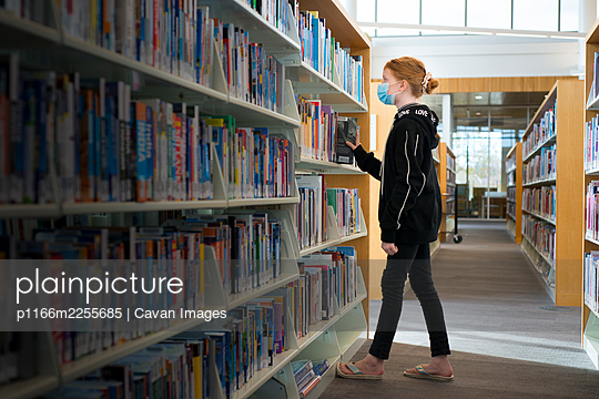 Young redhead girl with mask on in library looking at books. - p1166m2255685 by Cavan Images