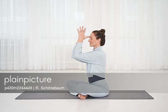 Woman practicing yoga in gym - p430m2244449 by R. Schönebaum