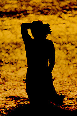 Woman in the sea at sunset - p1028m2087102 von Jean Marmeisse