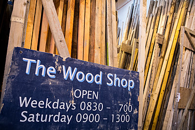Close up of old blue Open sign for Wood Shop leaning against a stack of wooden planks. - p1100m1575724 by Mint Images