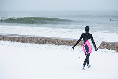 Woman going surfing during winter snow - p1166m2177114 by Cavan Images