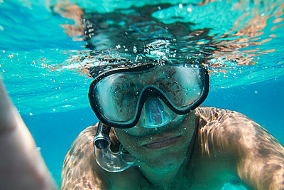 Portrait of man with diving goggles and snorkel taking selfie under water - p300m2120431 by Ivan Gener