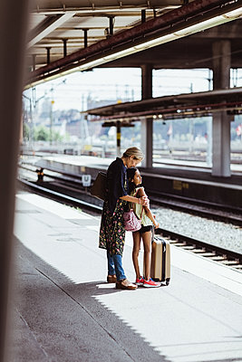 Full length of mother and daughter waiting at railroad station platform - p426m2146024 by Maskot
