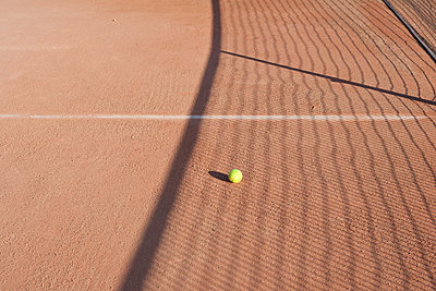 Shadow of net in tennis court over tennis ball - p623m874353f by Laurence Mouton