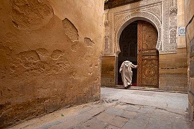 A man walks into a horseshoe shaped doorway; Fez, Morocco - p644m728762 by Ian Cumming