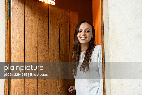 Portrait of smiling young woman standing near door - p623m2294895 by Eric Audras