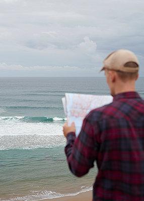 Mann mit Landkarte am Meer - p1124m1112513 von Willing-Holtz