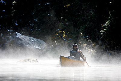 Middle age bearded man paddles boat on a foggy lake in Canada - p1166m2235087 by Cavan Images