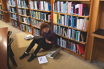 College student reading a book in library - p1315m2055904 by Wavebreak
