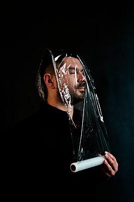 Mann mit Frischhaltefolie über dem Gesicht - p1521m2157610 von Charlotte Zobel