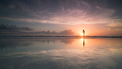 Silhouette woman at sea shore against cloudy sky during sunset, Daytona, Florida, USA - p301m1498816 by Brian Caissie
