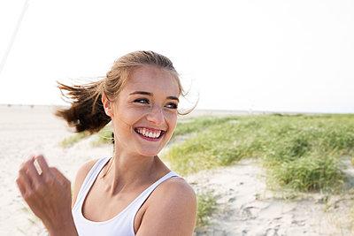 Glückliche junge Frau am Strand von St. Peter Ording - p341m1480685 von Mikesch