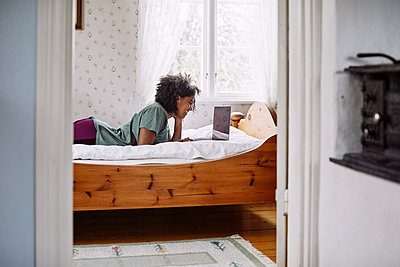 Side view of young woman using laptop while lying on bed at home seen through doorway - p426m2117185 by Maskot