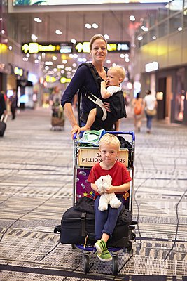 Portrait of mid adult woman and two children at Singapore Airport - p429m1022865 by Stephen Lux