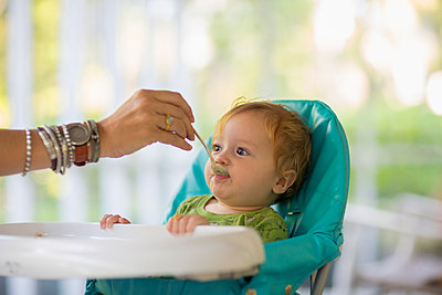 Caucasian mother feeding baby in high chair - p555m1415320 by Marc Romanelli