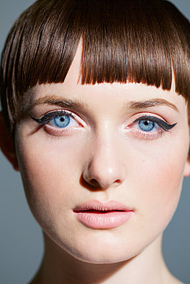 Young Woman with Blue Eyes and Black Eyeliner, Close-up view - p669m1146552 by Jutta Klee