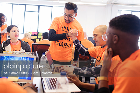Hackers handshaking, celebrating and coding for charity at hackathon