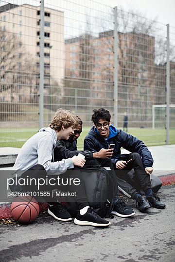 Full length of social media addicted friends wearing warm clothing while sitting on sidewalk after basketball practice d - p426m2101585 by Maskot