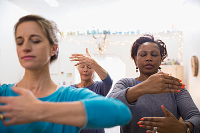 Serene women practicing tai chi in exercise class - p1192m1212868 by Hero Images
