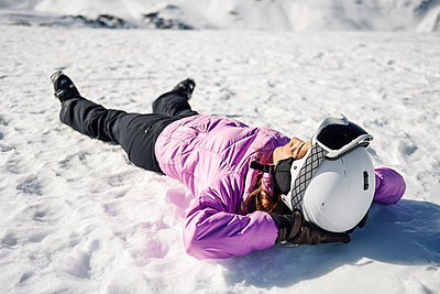 Woman taking a break after skiing lying on the snowy ground in Sierra Nevada, Andalusia, Spain - p300m2114519 by Javier Sánchez Mingorance