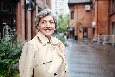 Smiling mature woman wearing trench coat while looking away - p300m2277698 by Katharina und Ekaterina
