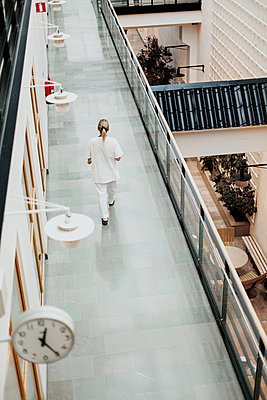 Female doctor walking through corridor - p312m2174382 by Scandinav