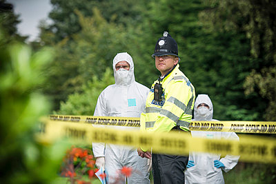 Policeman guarding forensic crime scene - p429m711792f by Monty Rakusen