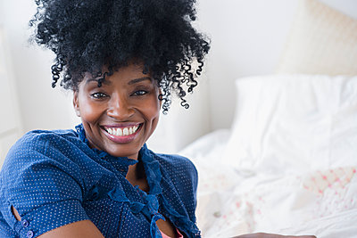 Black woman smiling on bed - p555m1415276 by JGI/Jamie Grill