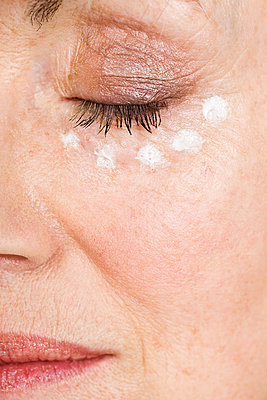 Woman with eye cream - p9245839f by Image Source
