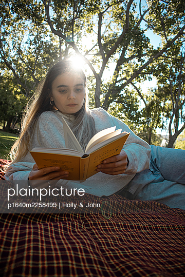 Teenage girl reading a book in the park - p1640m2258499 by Holly & John