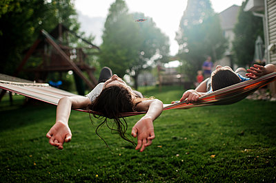 Brother and sister relaxing in hammock together in backyard - p1166m2146840 by Cavan Images