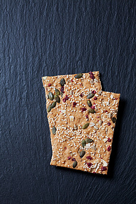 Two slices of crispbread with cranberries, coconut and pumpkin seed on slate - p300m1417317 by Dieter Heinemann