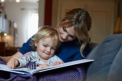 Mother and little daughter sitting on the couch at home watching book - p300m1535819 by Rainer Berg