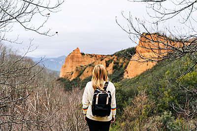 Female hiker on a viewpoint, looking to Mina de Oro Romana, former gold mine, Las Medulas, Castile and Leon, Spain - p300m2170557 by Daniel González