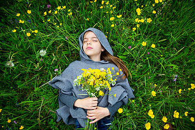Girl picking yellow wildflowers - p300m2198589 by Larissa Veronesi