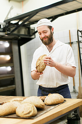 Sweden, Baker holding bread in commercial kitchen - p352m1079182f by Christian Ferm