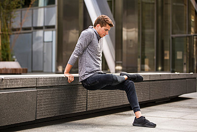 Young runner stretching on pavement, London, UK - p429m2075357 by Tom Dunkley