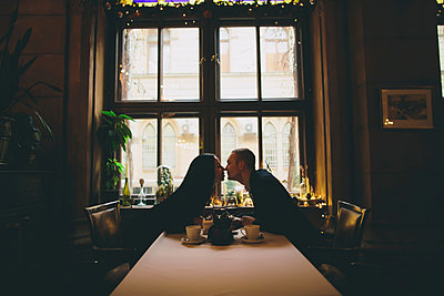 Caucasian couple sitting at table rubbing noses - p555m1532675 by Kateryna Soroka