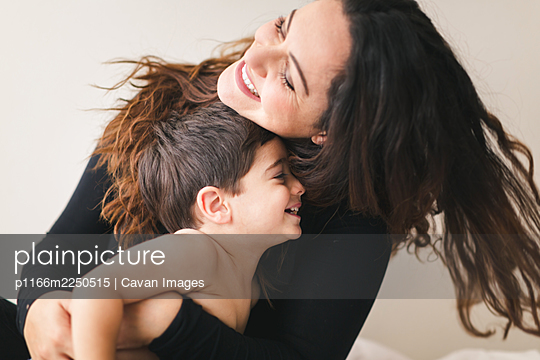 Mother and son hugging each other and laughing. - p1166m2250515 by Cavan Images