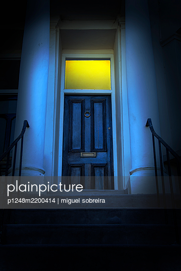 Illuminated front doorway at night - p1248m2200414 by miguel sobreira