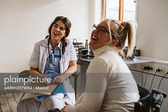 Cheerful female healthcare worker and disabled patient looking away - p426m2279854 by Maskot