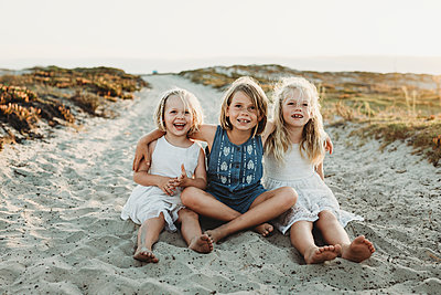 Portrait of three young sisters embracing and smiling in sand - p1166m2165898 by Cavan Images