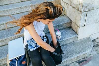 Young woman with laptop and smoothie looking in the backpack - p300m1494761 by Kiko Jimenez